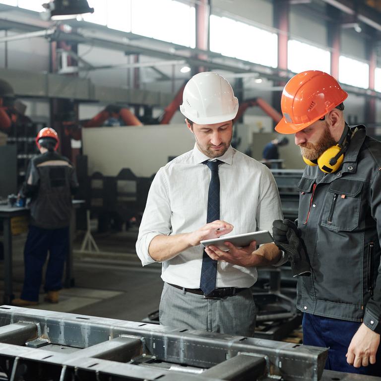 Zwei Arbeiter stehen in Werkshalle und schauen auf ein Tablet.