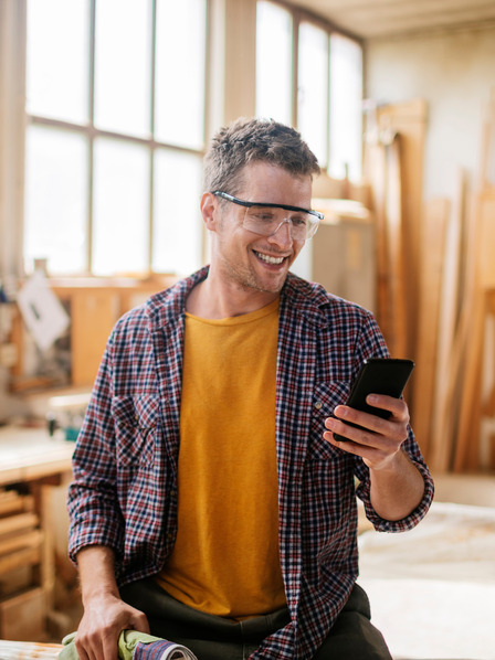 Handwerker steht in Werkstatt und schaut auf sein Handy