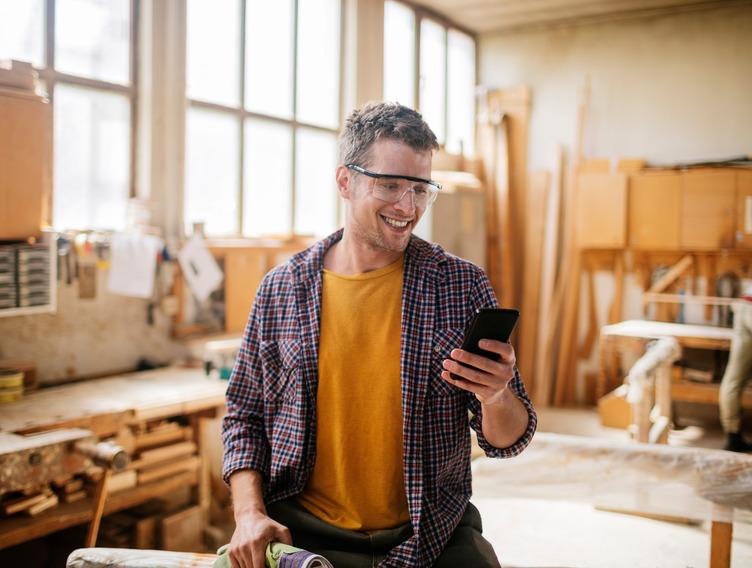 Handwerker nutzt in der Werkstatt sein Smartphone.