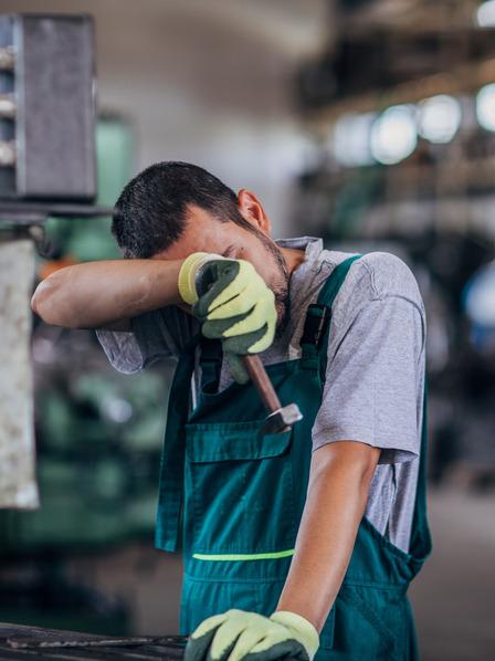 Handwerker steht in der Werkstatt und wischt sich den Schweiß von der Stirn