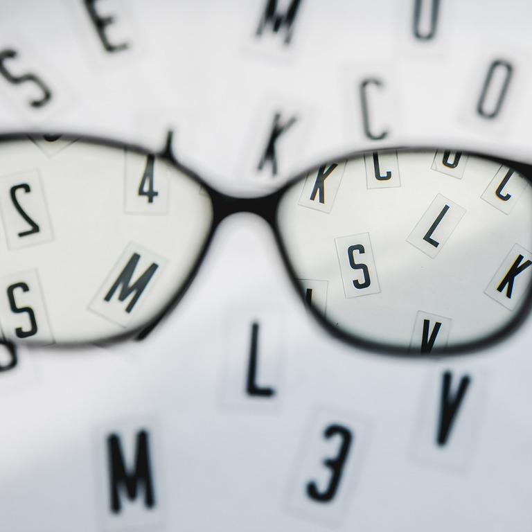 Blick durch eine Brille auf unscharfe Buchtsaben beim Augenarzt