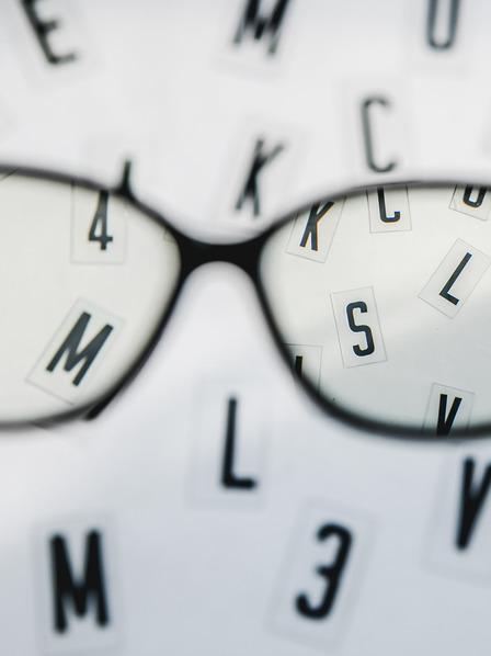 Brille vor verschwommenen Buchstaben.