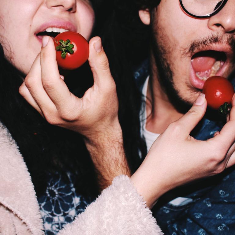 Eine Frau und ein Mann stekcen sich gegenseitig Tomaten in den Mund.