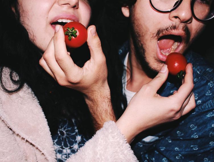 Ein Mann und eine Frau füttern sich gegenseitig mit Cherrytomaten.
