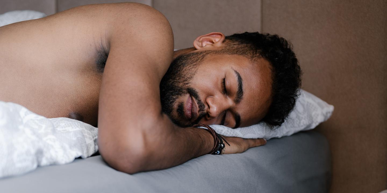 junger Mann schläft entspannt in seinem Bett