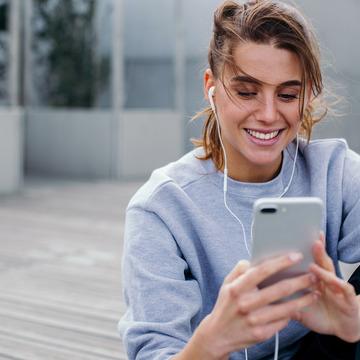 Junge Frau sitzt auf Terrasse mit Smartphone und Köpfhörern