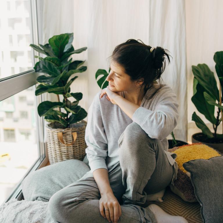 Frau sitzt traurig auf ihrem Bett und schaut aus dem Fenster.