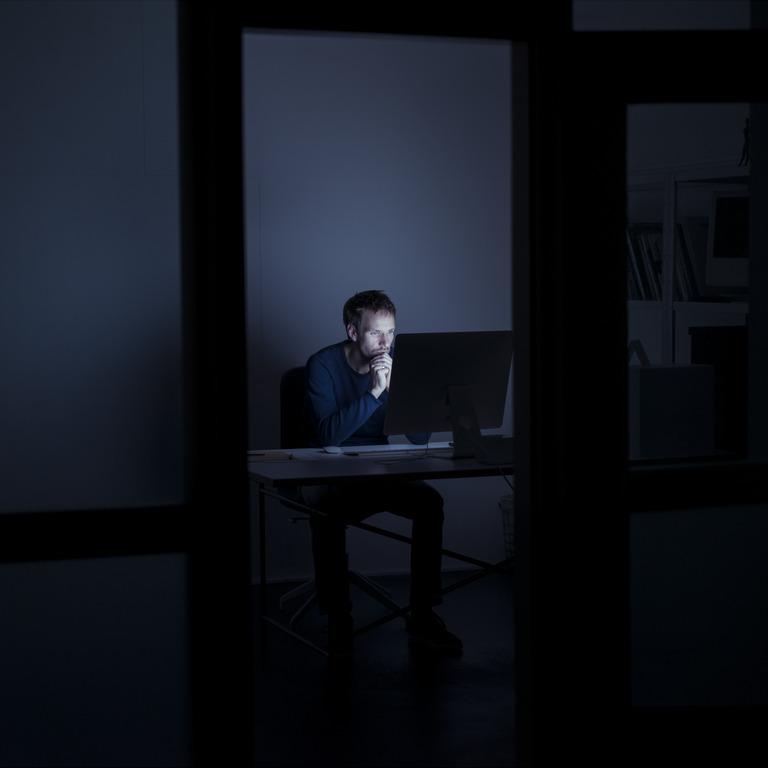 Mann sitzt im dunklen Büro vor dem PC