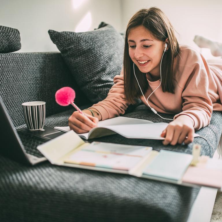 Junge Frau liegt auf Sofa und lernt mit Laptop und Unterlagen.