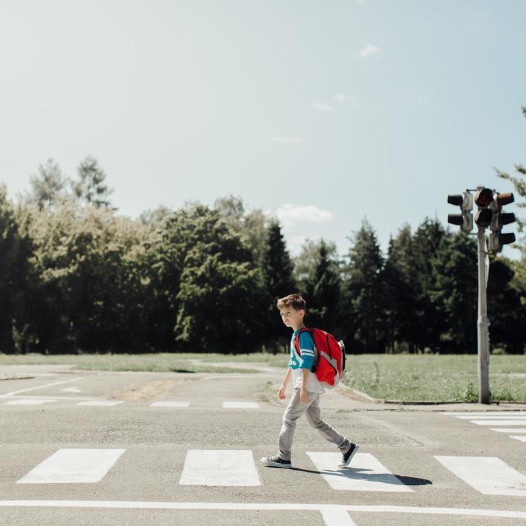 Grundschüler überquert einen Zebrastreifen