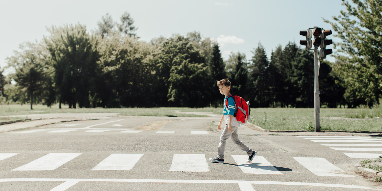 Schulkind geht über Zebrastreifen