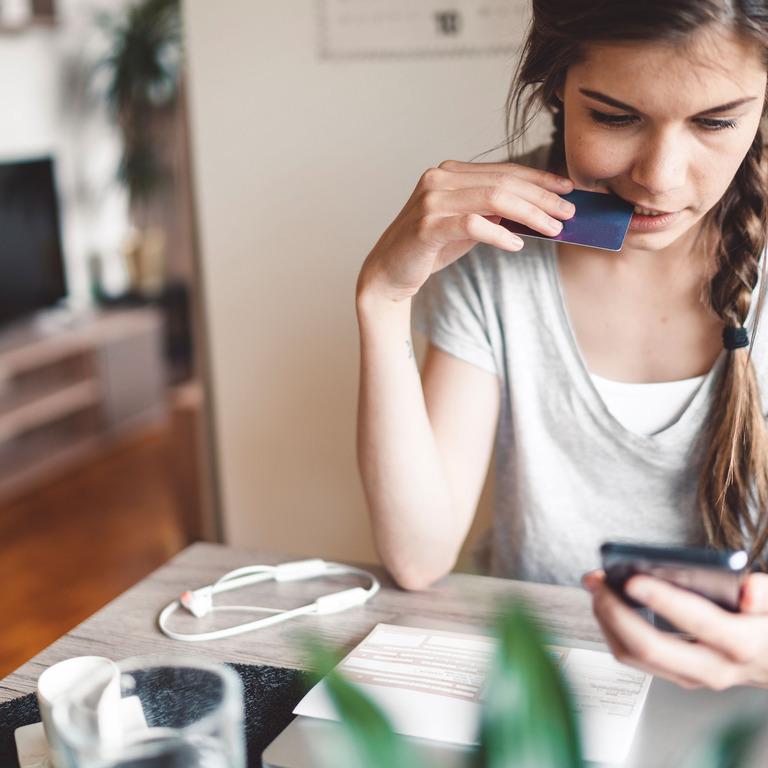 Junge Frau schaut auf ihr Smartphone.
