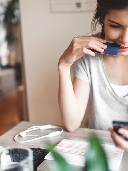 Junge Frau beißt leicht in ihre Kreditkarte und schaut unglücklich auf ihr Handy.