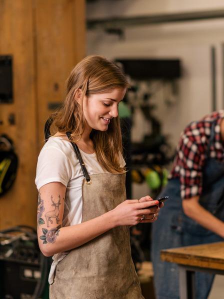 Junge Auszubildene steht in der Werkstatt und schaut auf ihr Handy