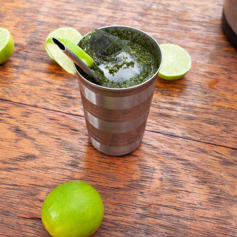 Ein Becher mit Maté-Tee, Eiswürfeln und Limetten.