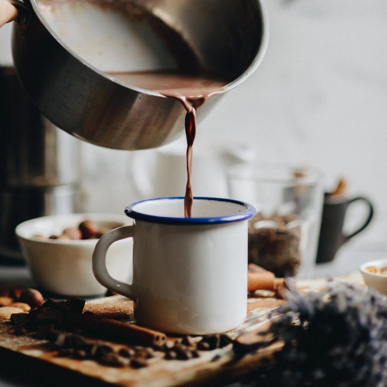 Heißer Kakao der aus dem Topf in eine Tasse geschüttet wird.