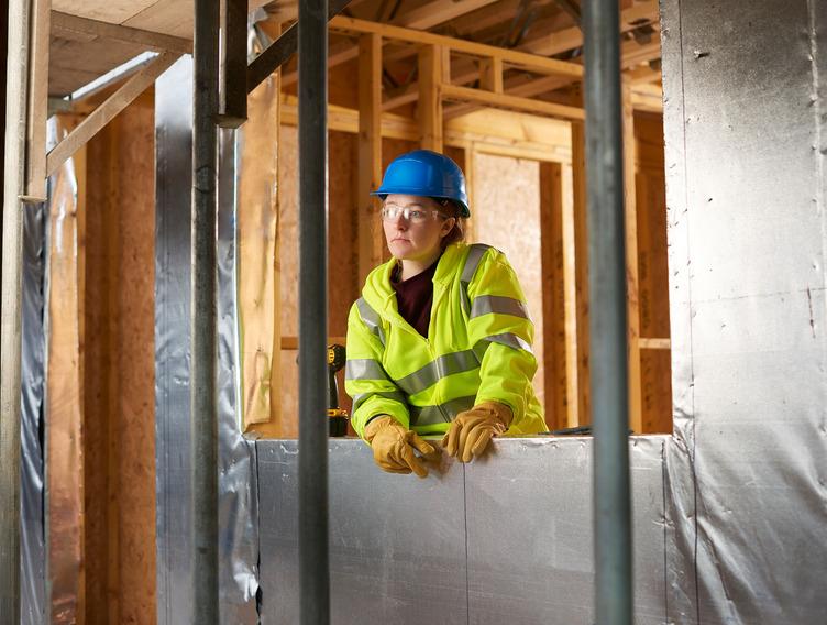 Bauarbeiterin mit Helm und Sicherheitsweste blickt unzufrieden auf Baustelle