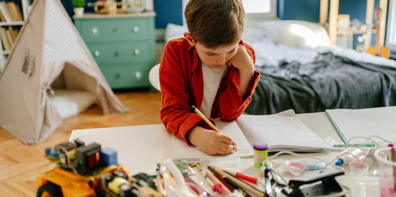 Junge sitzt an seinem Schreibtisch Zuhause und macht Schulaufgaben.