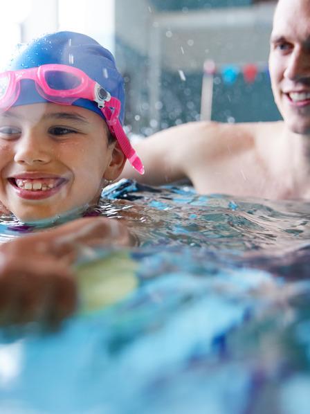 Kind lernt mit Vater schwimmen in der Schwimmhalle