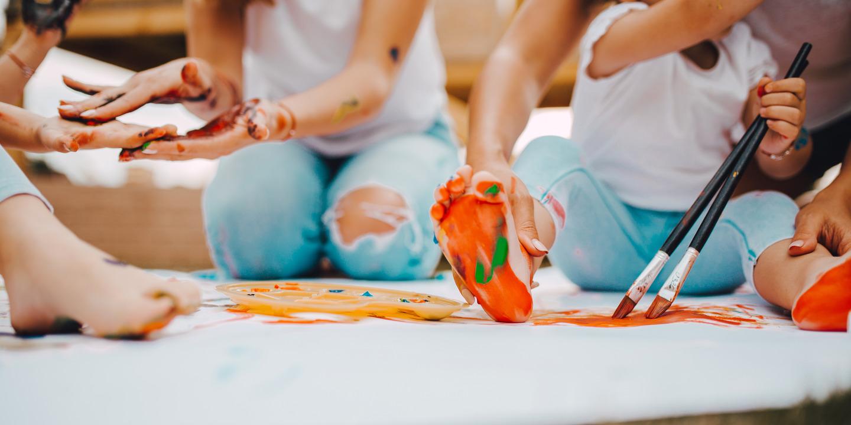 Kinder und Erzieher malen gemeinsam auf dem Fußboden. Die Fußsohle des Kindes ist orange mit grünen Tupfen angemalt.