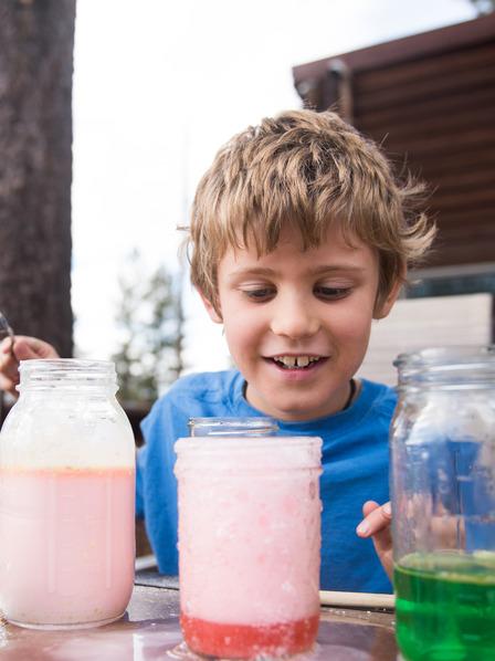 Junge experimentiert im Garten mit Flüssigkeiten