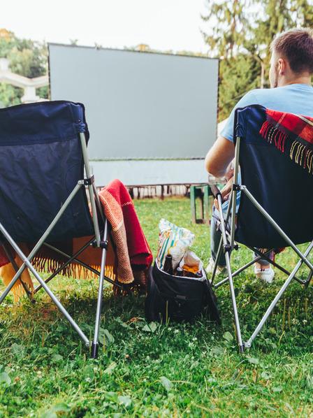 Mann sitzt auf einem Campingstuhl im Open Air Kino