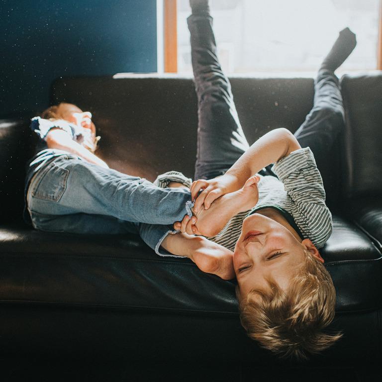 Ist Bewegungsdrang ein Zeichen von ADHS? Zwei Kinder toben auf dem Sofa.
