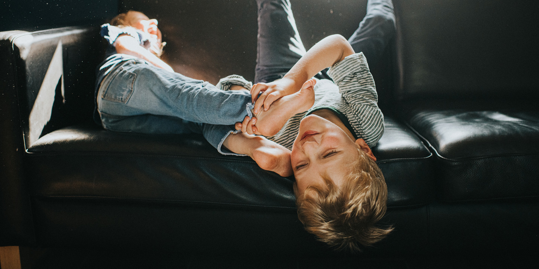 Ist Bewegungsfreude bereits ADHS? Zwei Kinder toben auf dem Sofa.
