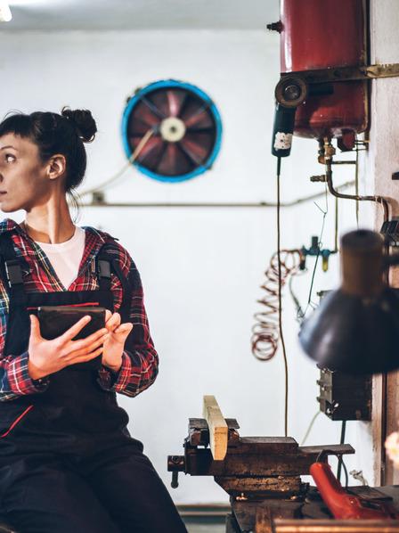 Handwerkerin steuert ihre Werkstatt mithilfe von Smart-Building-Technologie