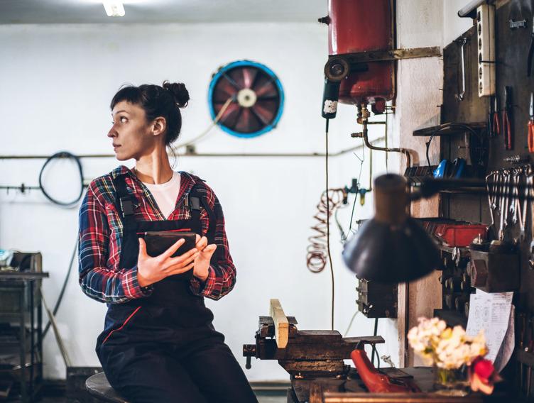 Frau in Arbeitskleidung sitzt mit einem Tablet in der Hand auf einer Werkbank
