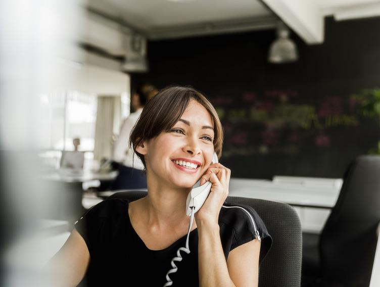 Mitarbeiterin sitzt im Büro und führt ein Kundengespräch am Telefon