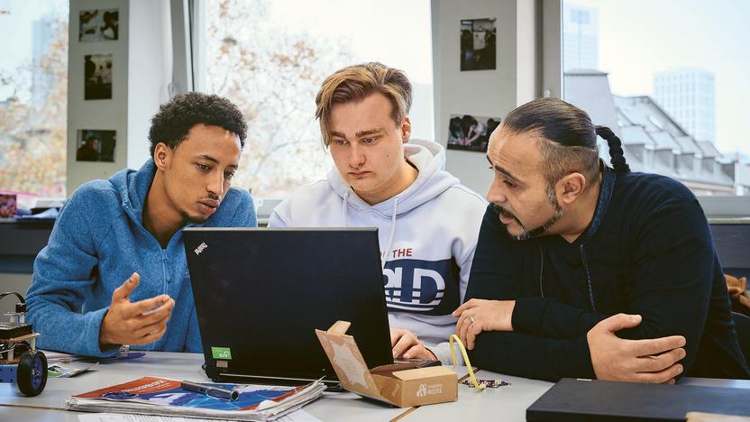 Zwei Auszubildene sitzen mit ihrem Lehrer zusammen am Laptop