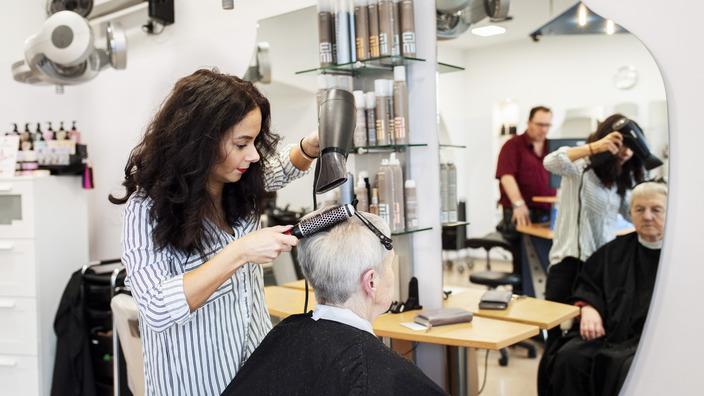 Friseurin schneidet Kundin die Haare