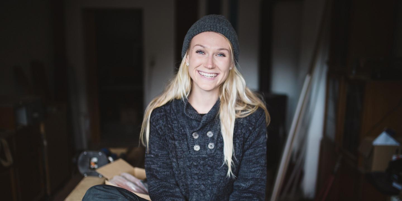 Junge Handwerkerin sitzt in der Werkstatt und lächelt in die Kamera