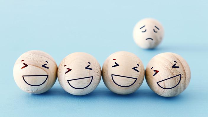 Vier Holzkugeln mit lachenden Gesichtern, eine Kugel mit traurigem Gesicht im Hintergrund.