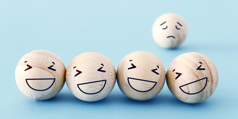 Vier lachende Smileys im Vordergrund und ein trauriger im Hintergrund