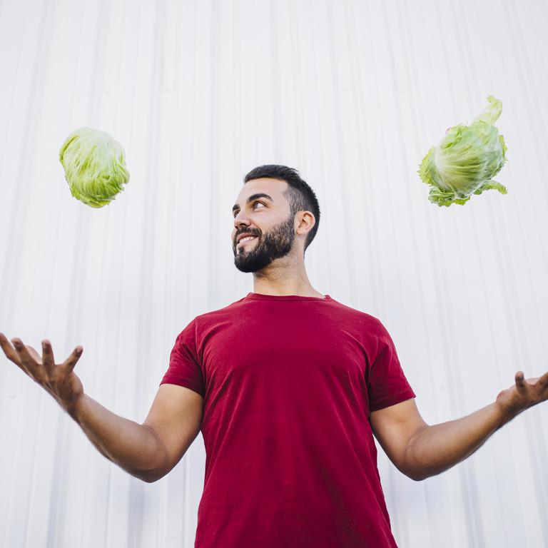 Sportlicher Mann wirft in jeder Hand einen Salat in die Luft