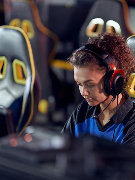 Junge Frau sitzt bei einem Gaming Wettbewerb und spielt