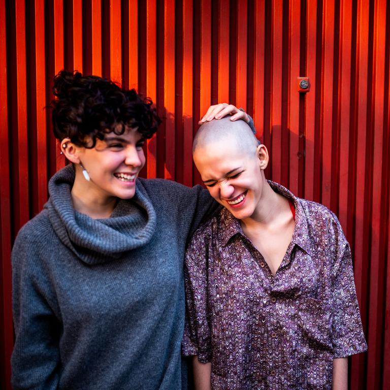 Zwei Frauen üben sich in Optimismus und lachen zusammen