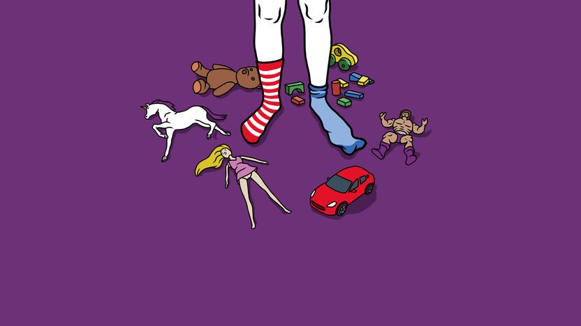 Kind steht inmitten von Spielzeug, das allgemein einem bestimmten Geschlecht zugewiesen wird, wie Auto, Barbie, Bauklötze.