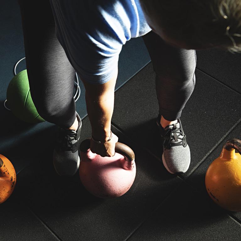 Person trainiert Kraft mit Gewichten