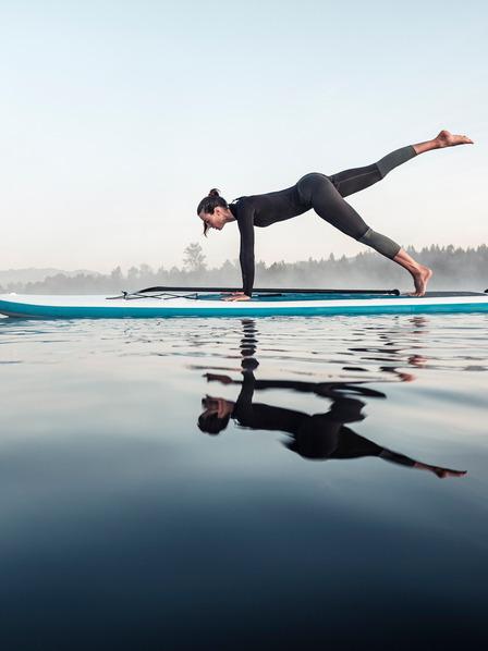Frau macht Gymnastik-Pose auf einem Surfbrett auf dem Wasser