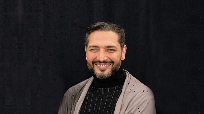 Gianni Jovanovic ist lächelnd vor einem schwarzen Hintergrund zu sehen.