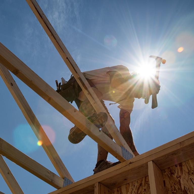 Ein Handwerker arbeitet an dem Dach eines Holzhauses mit einem Hammer in der starken Mittagssonne