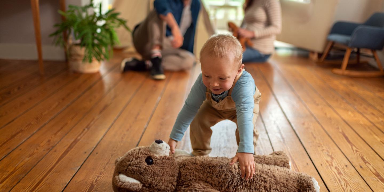 Kleinkind hebt Teddy-Bär vom Boden im Wohnzimmer auf.
