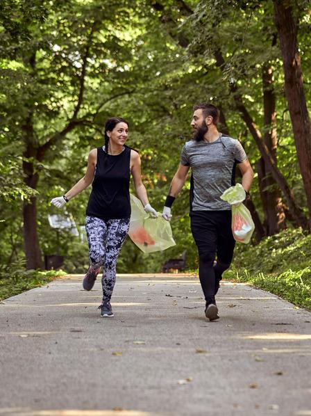 Mann und Frau joggen durch den Wald und sammeln Müll