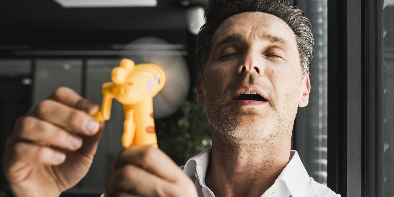 Schwitzender Mann benutzt kleinen Handventilator