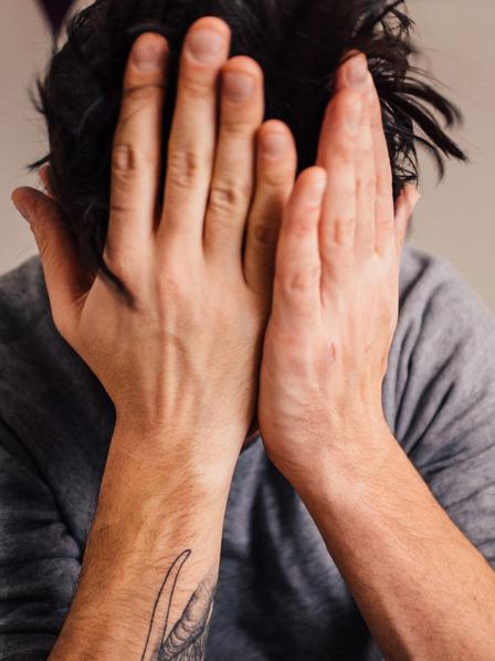 Mann hält die Hände vor den Kopf und sitzt auf dem Bett.