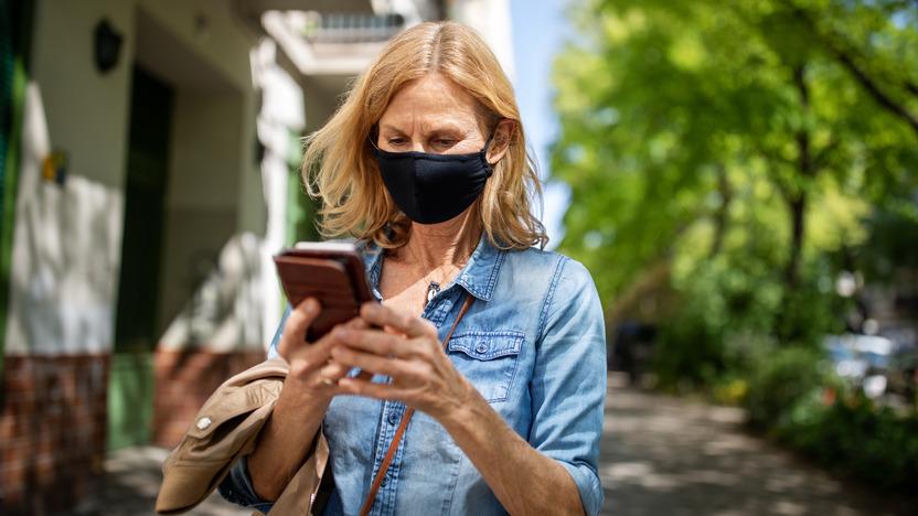 Frau mit Maske schaut im Freien auf ihr Handy.