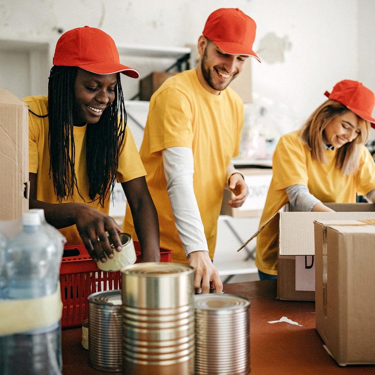 Junge Erwachsene voluntieren und helfen mit Lebensmitteln und packen.